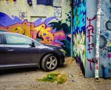 Parked Car Near Wall of Graffiti